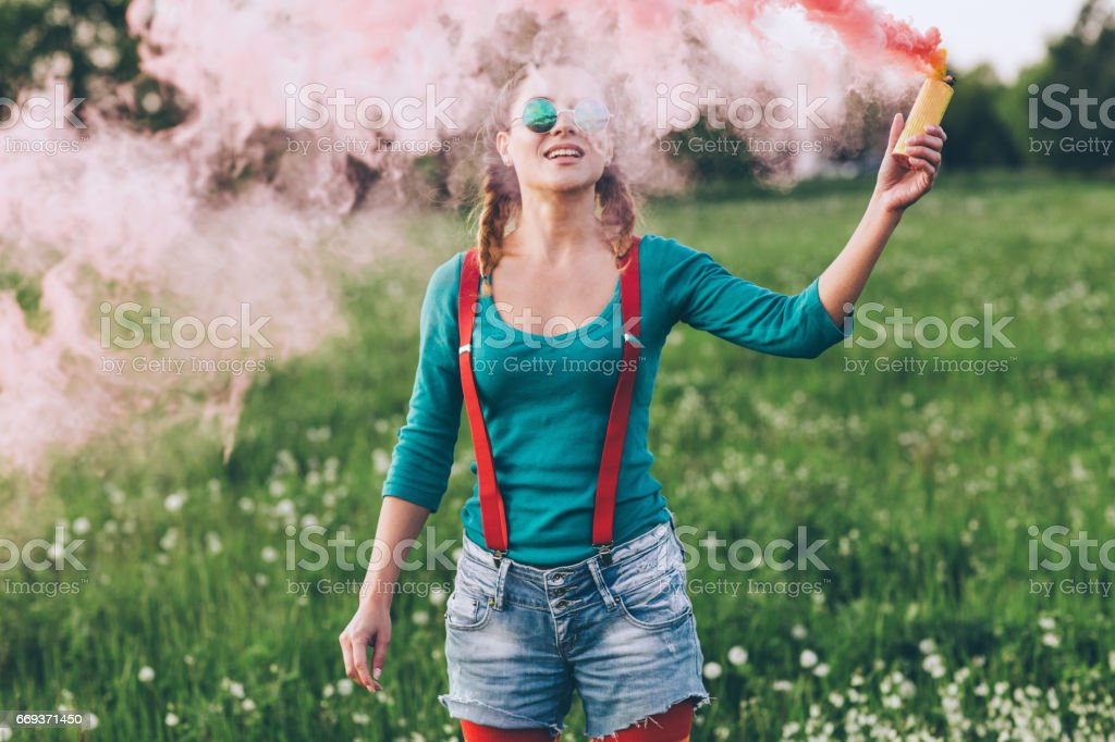 Young woman in a park with pink smoke stock photo