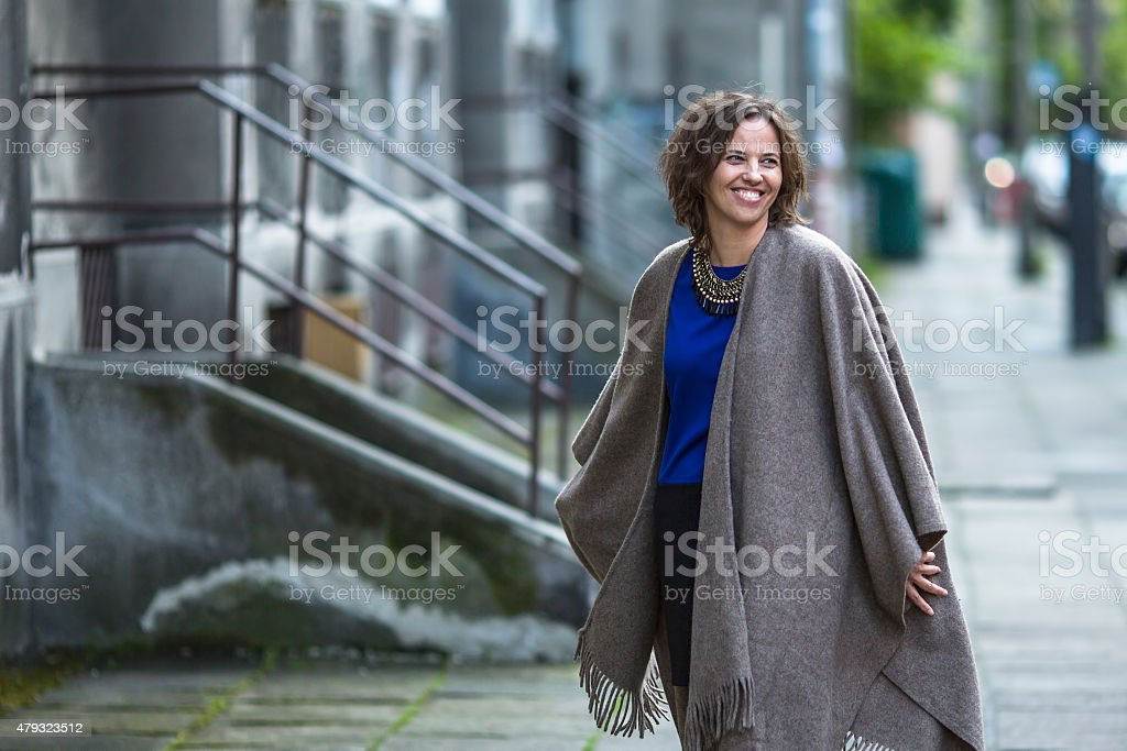 Young woman in a poncho at evening street. stock photo