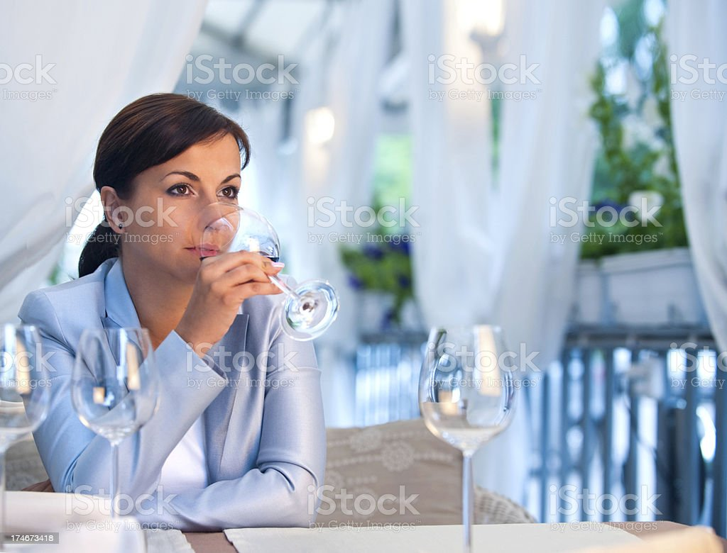 Young woman in a restaurant drinking wine royalty-free stock photo