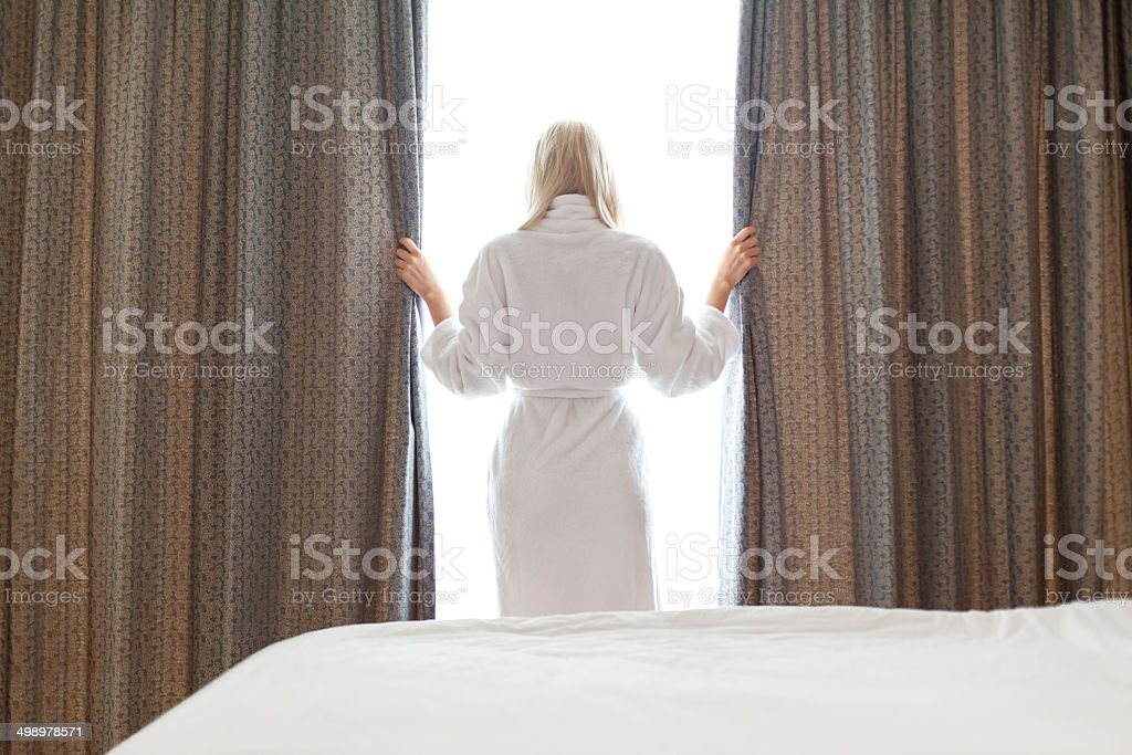 Young woman in a robe looks through window curtain stock photo