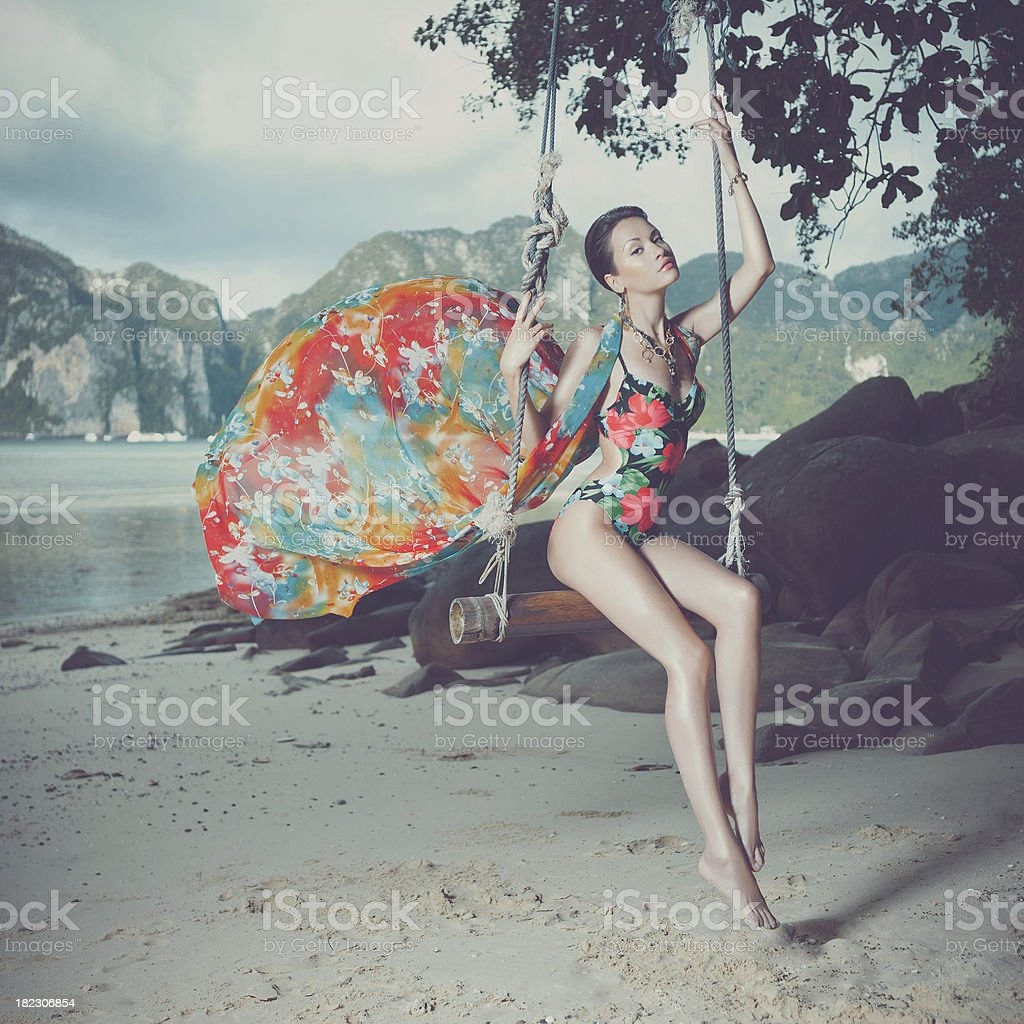 Young woman in a tree swing on the beach stock photo