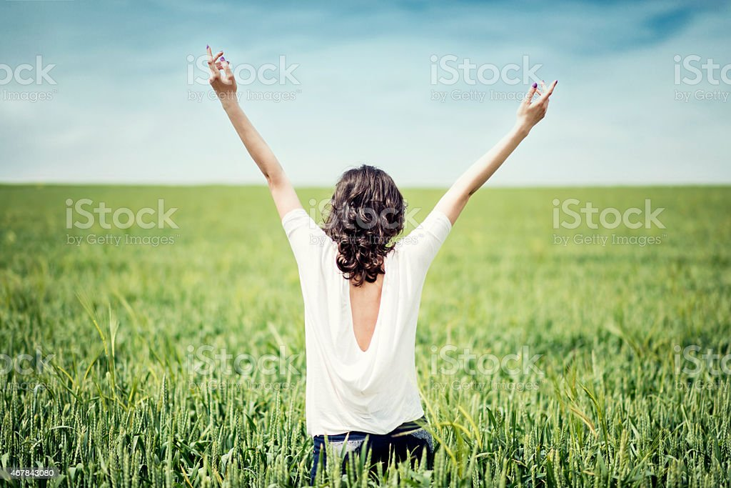 A young woman in a white top spreading her arms in the air stock photo