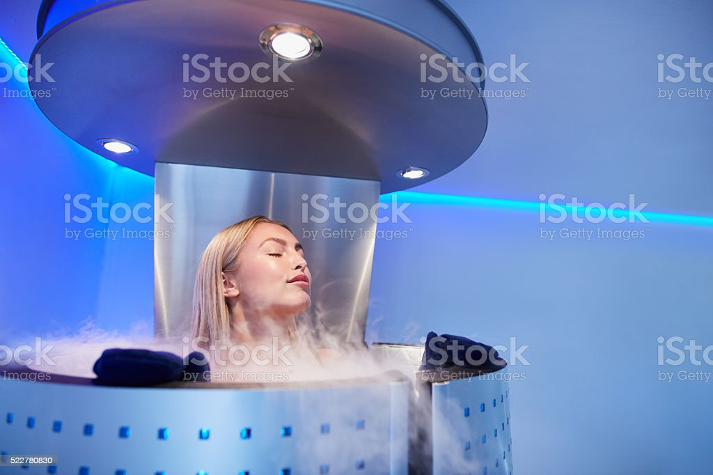 Young woman in a whole body cryo sauna stock photo