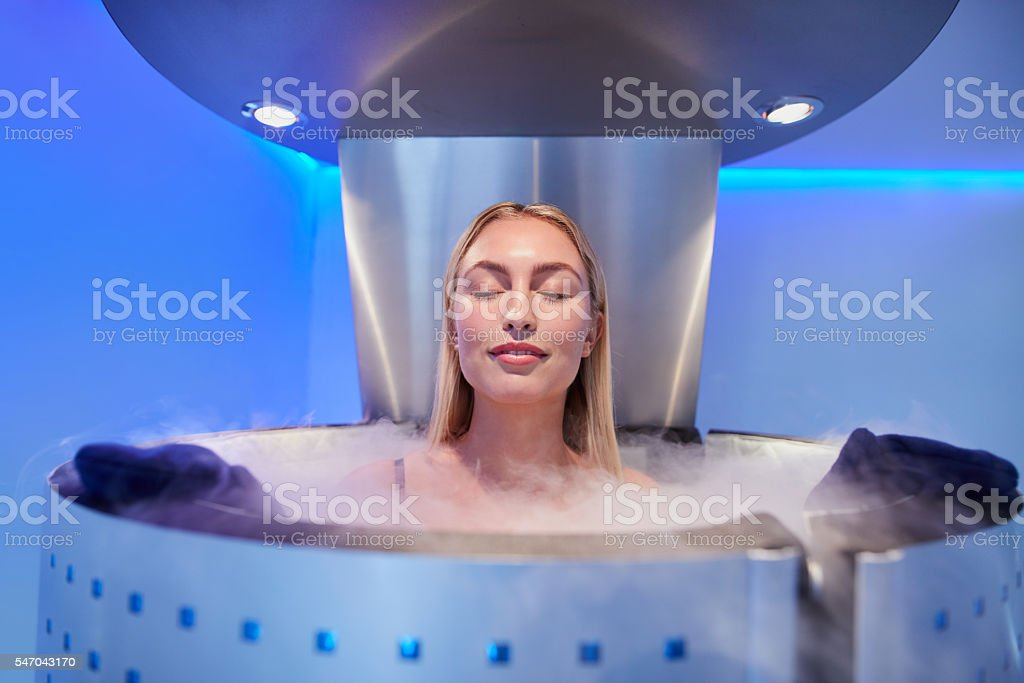 Young woman in a whole body cryotherapy cabin stock photo