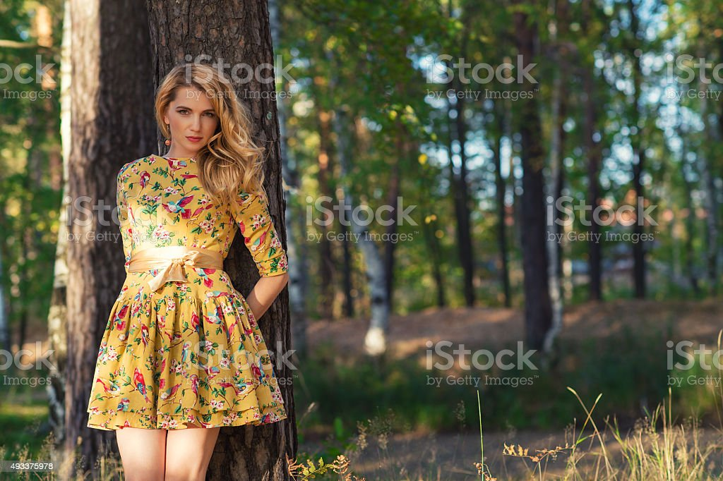 young woman in a yellow dress in the park stock photo