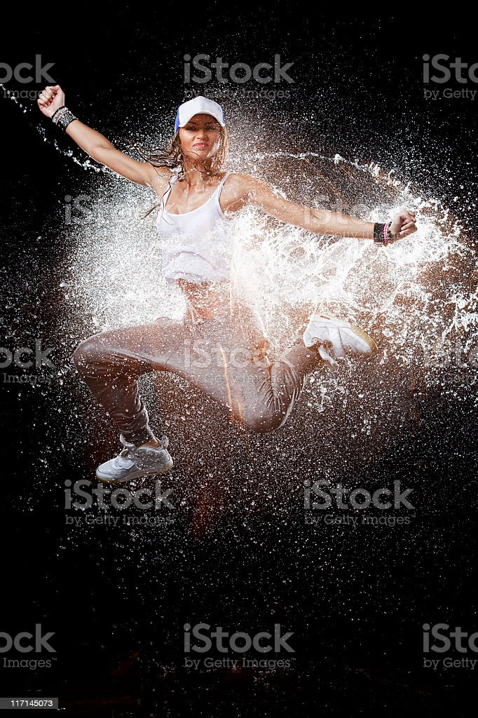 Young woman in activewear leaping through splashed water stock photo