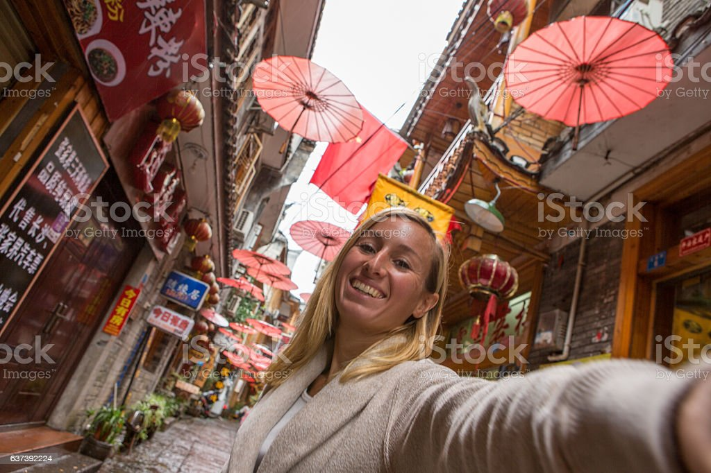 Young woman in alley of ancient village takes selfie, China stock photo