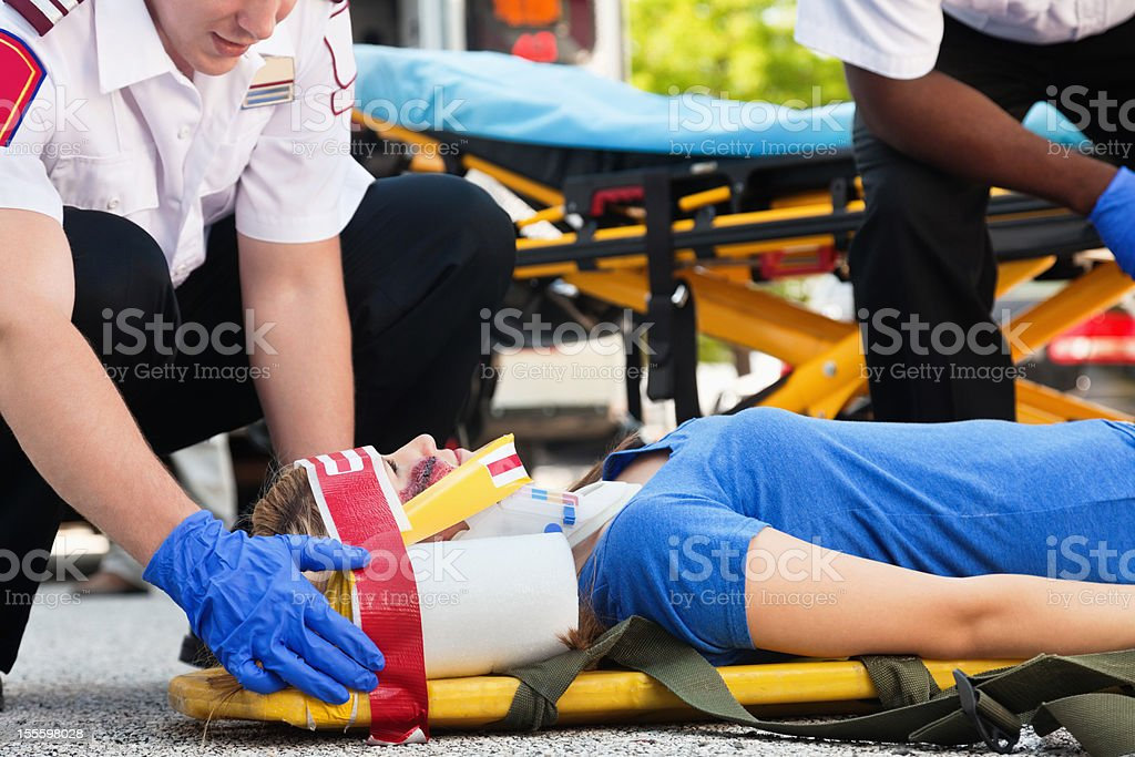 Young woman in an ambulance stretcher beinng treated by medics royalty-free stock photo