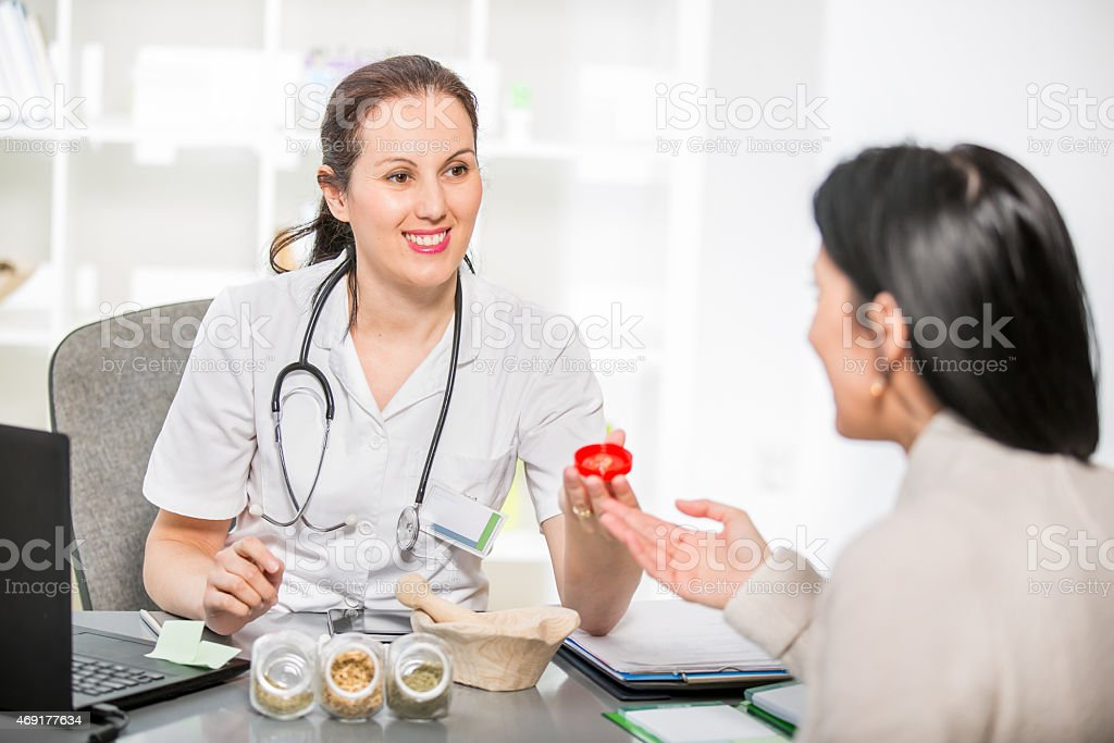 Young woman in an office at the doctor homeopaths stock photo