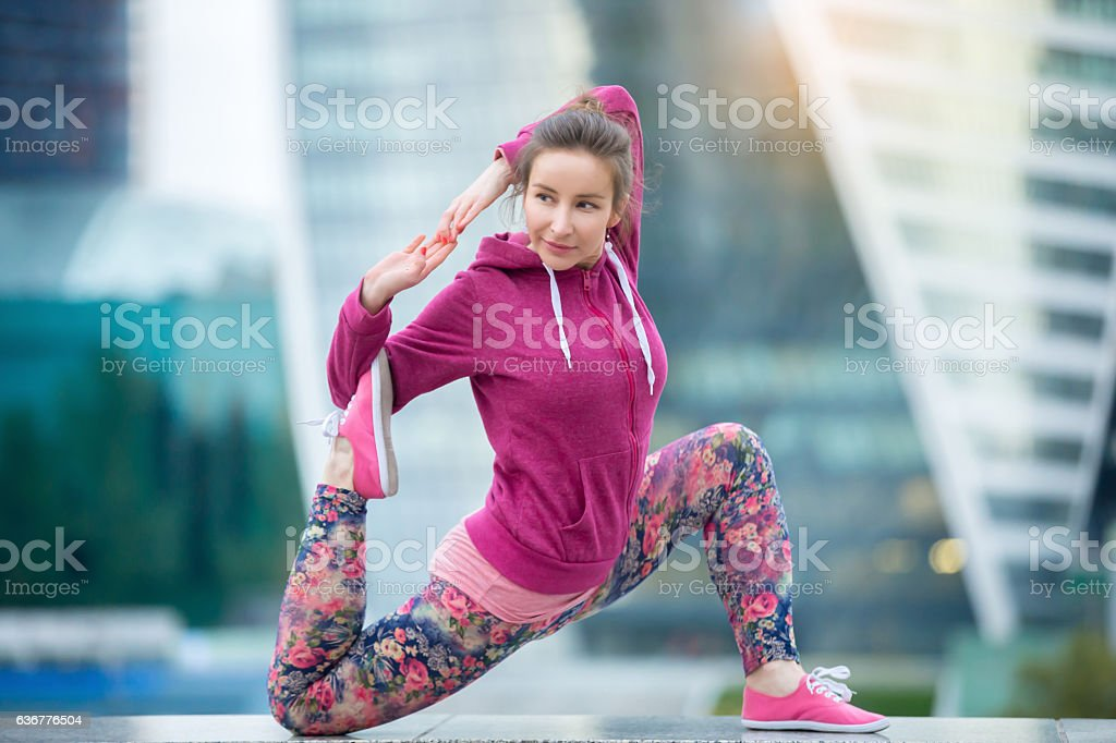 Young woman in anjaneyasana pose against the city stock photo