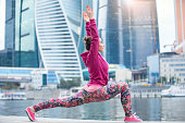 Young woman in anjaneyasana pose against the skyscrapers
