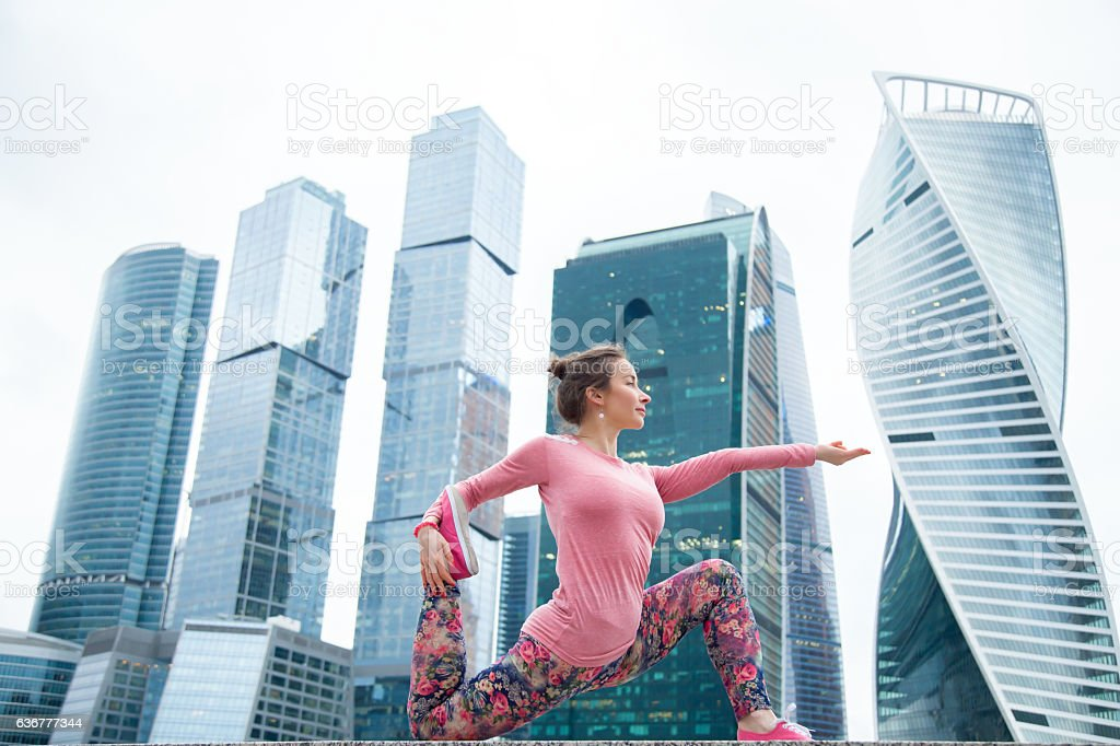 Young woman in anjaneyasana pose against the urban background stock photo