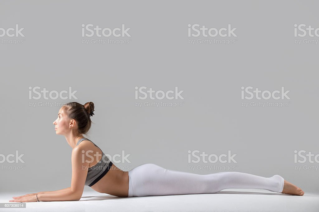 Young woman in Ardha bhudjangasana pose, grey studio background stock photo