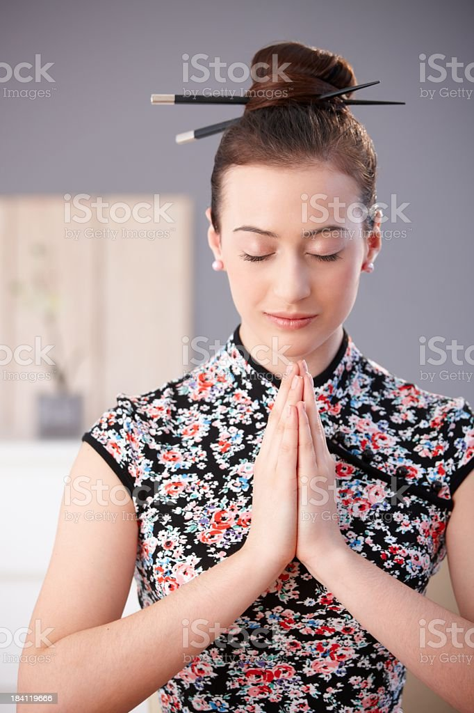Young woman in asian outfit praying royalty-free stock photo
