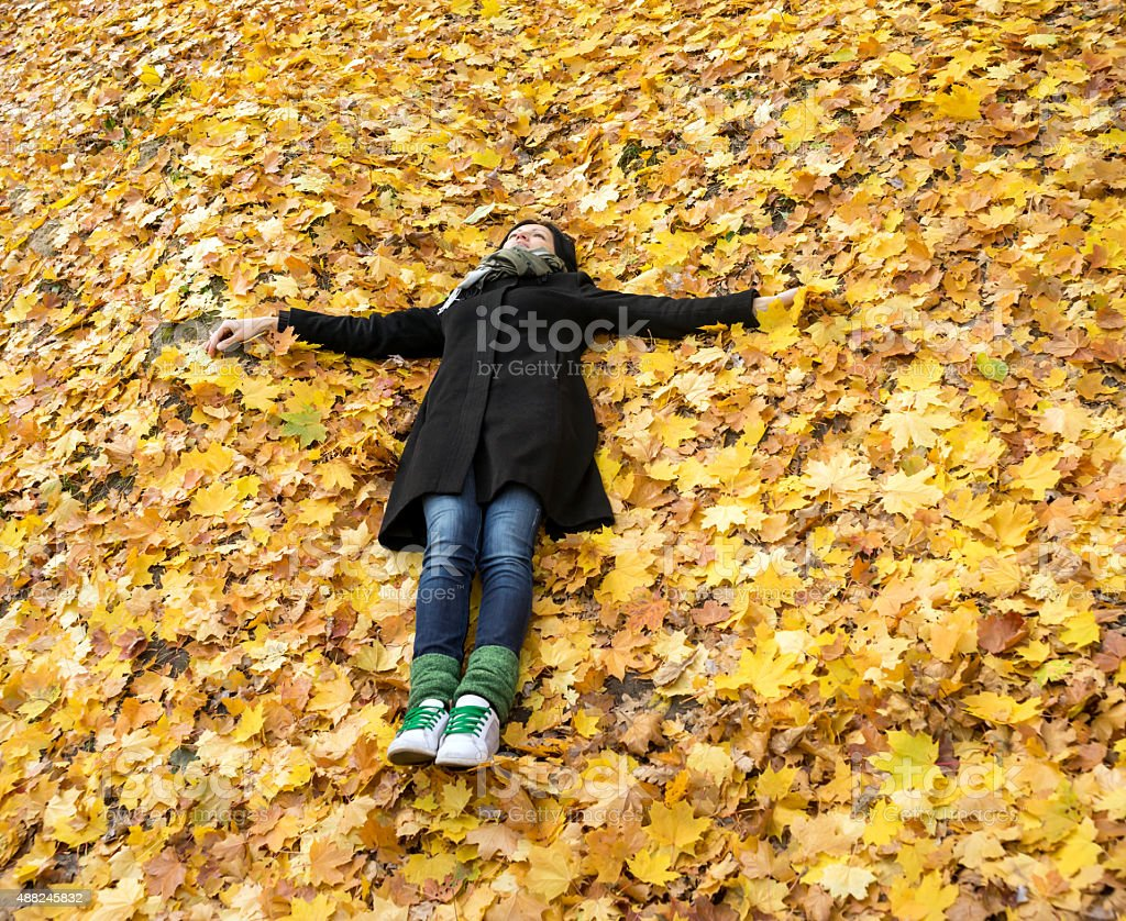 Young woman in autumn leaves stock photo