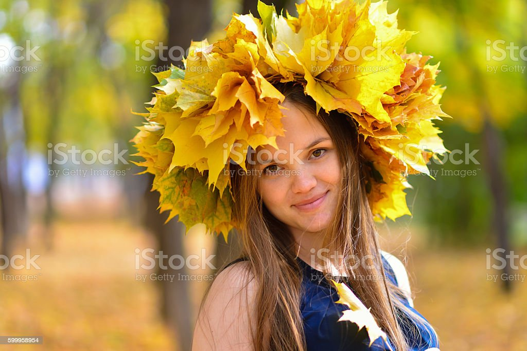 Young woman in autumn park with wreath of maple leaves. stock photo