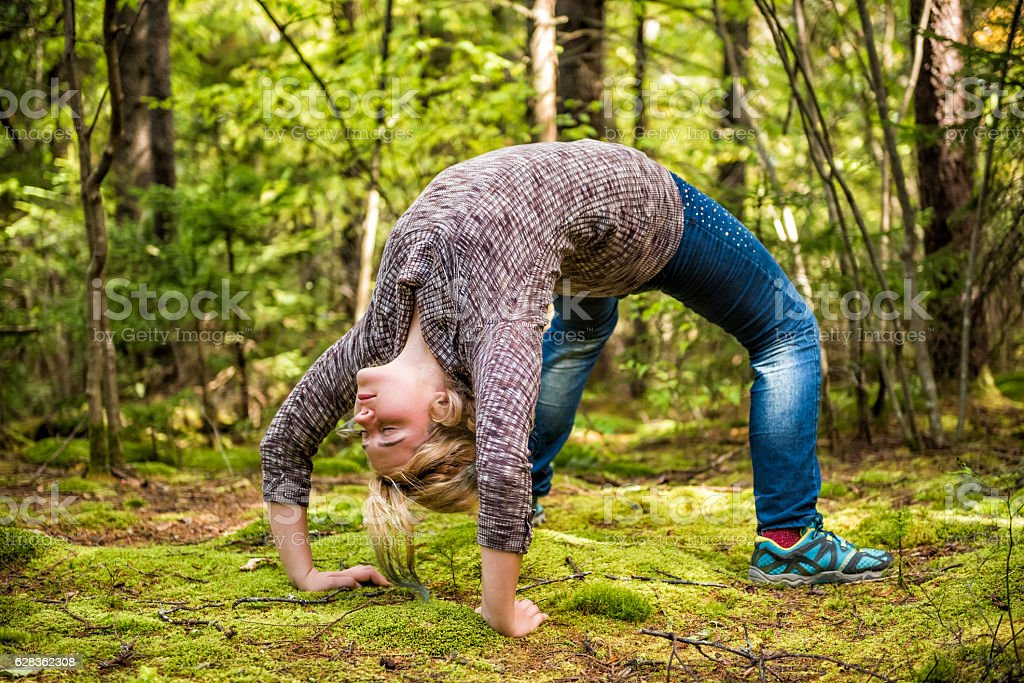 Young woman in back bend arch pose in mossy forest stock photo