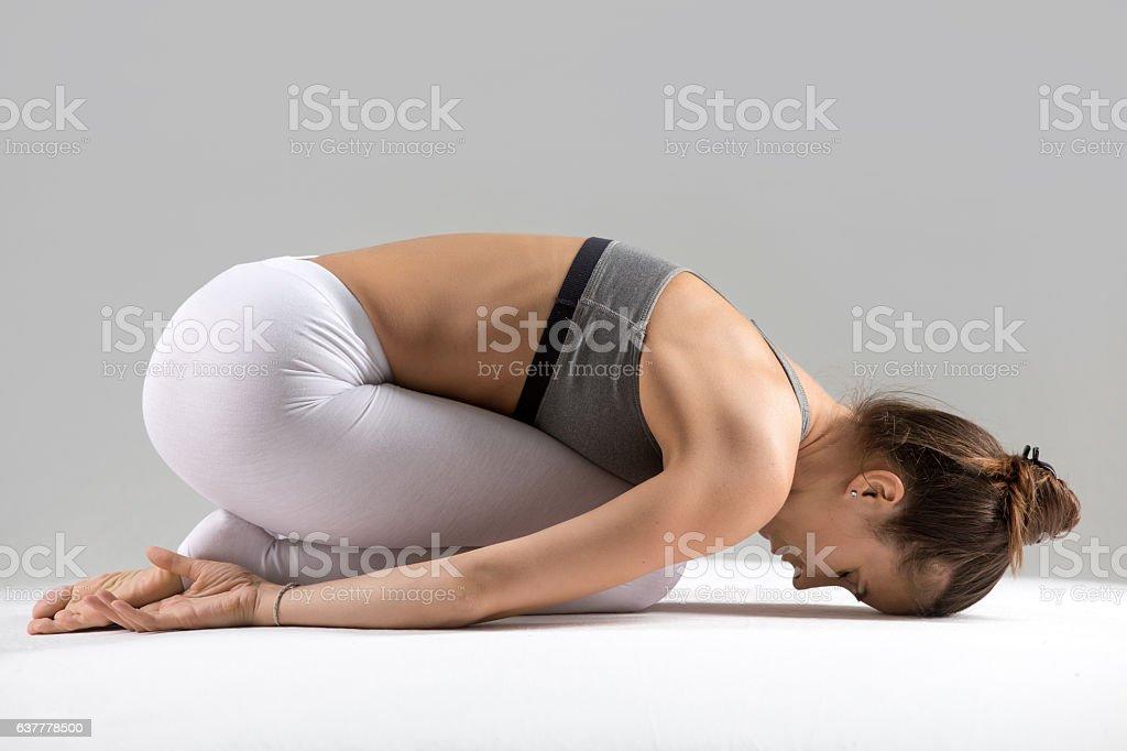 Young woman in Balasana pose, grey studio background stock photo