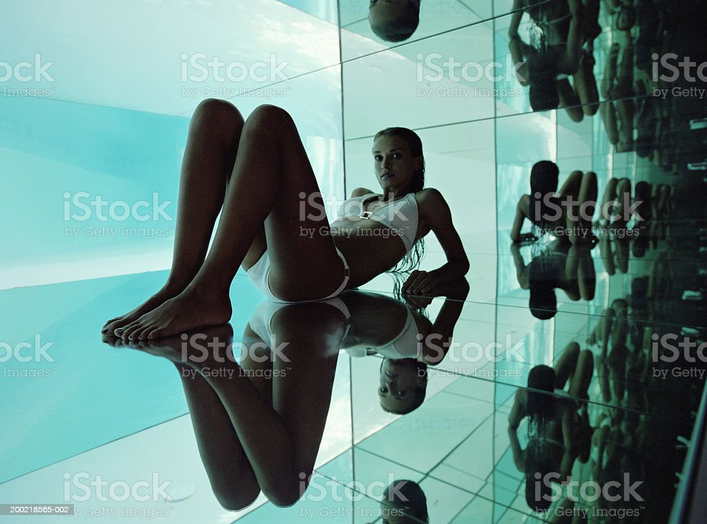 Young woman in bathing suit surrounded by mirrors royalty-free stock photo