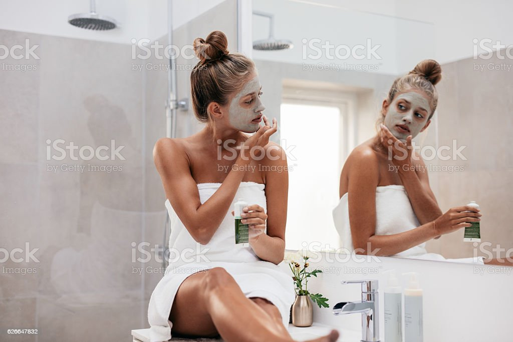 Young woman in bathroom applying facepack stock photo
