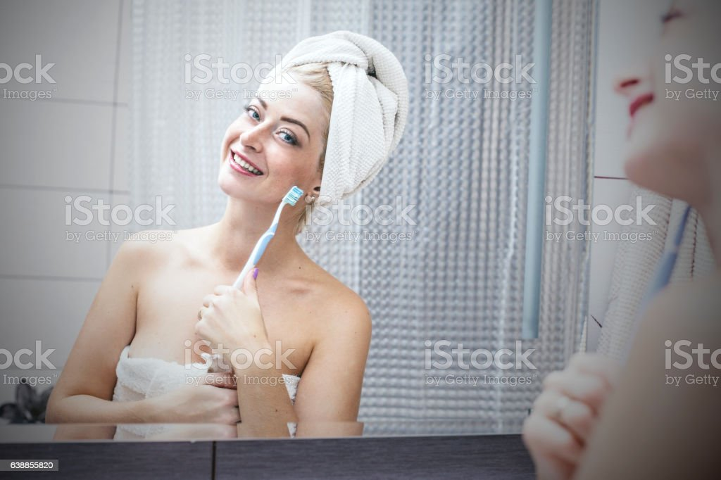 Young woman in bathroom brushing her teeth with a toothbrush stock photo