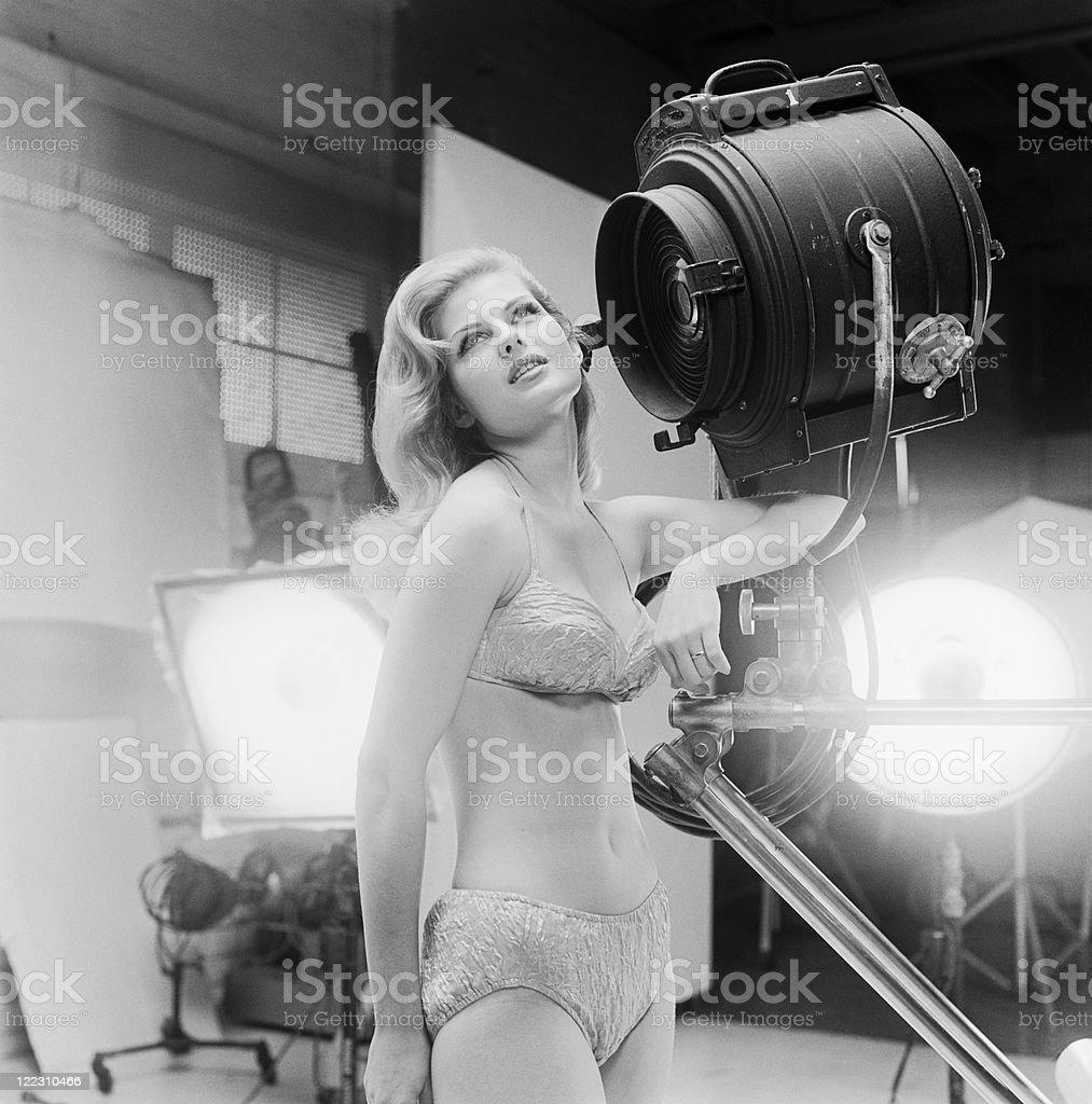 Young woman in bikini standing beside spotlight stock photo