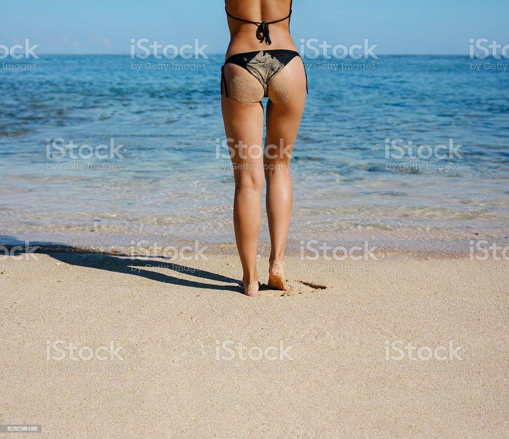 Young woman in bikini standing on the beach stock photo