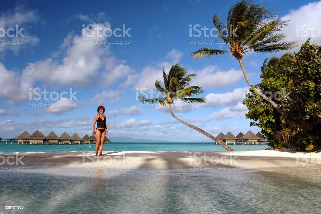 Young woman in black bathing suit on Bora Bora beach stock photo