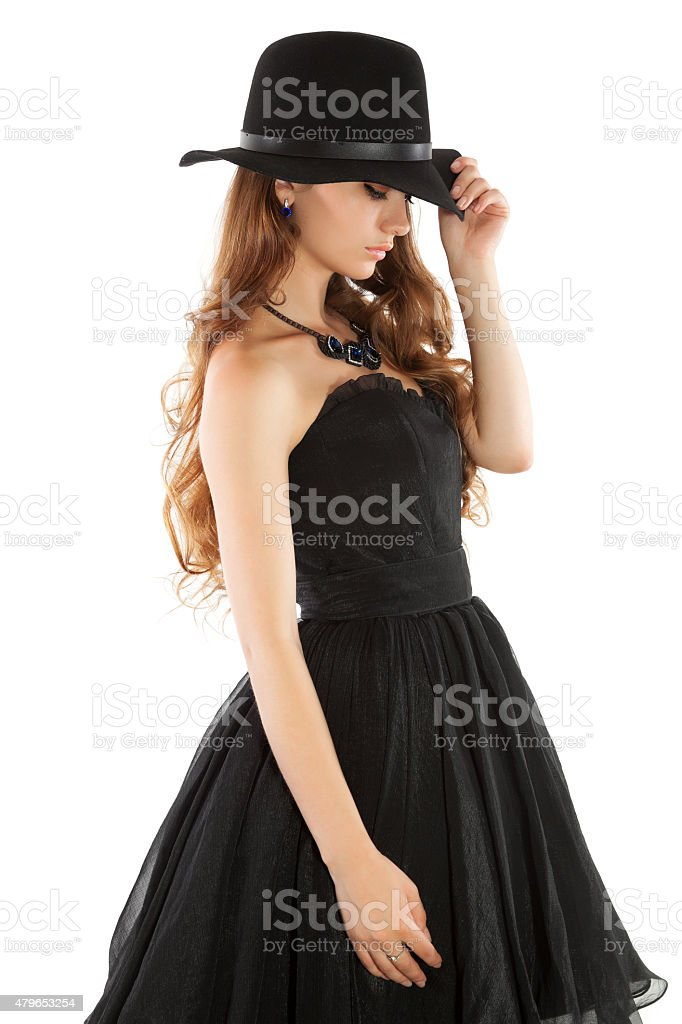 Young woman in black dress and hat pulling pent down stock photo