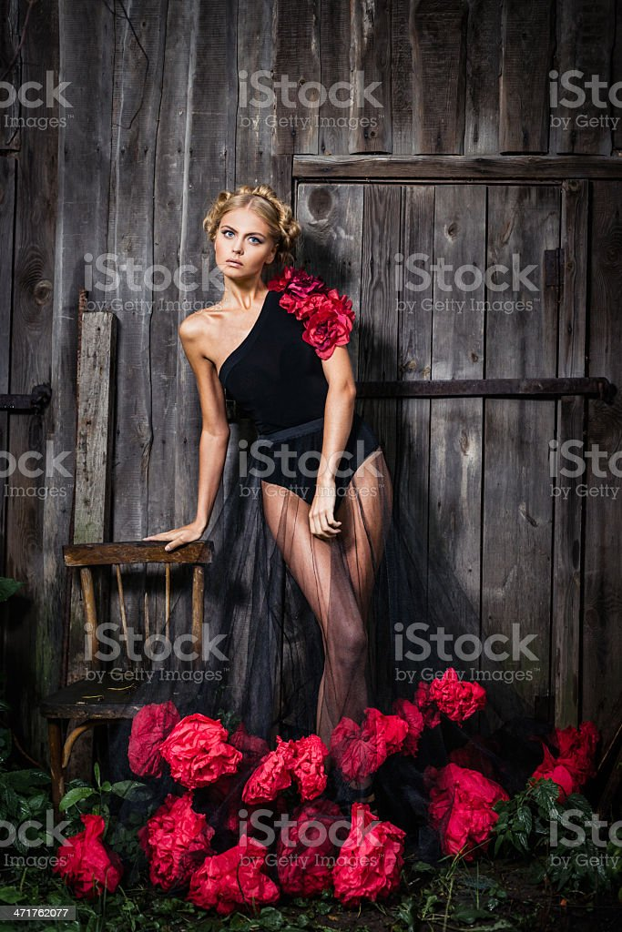 Young woman in black dress with flowers stock photo