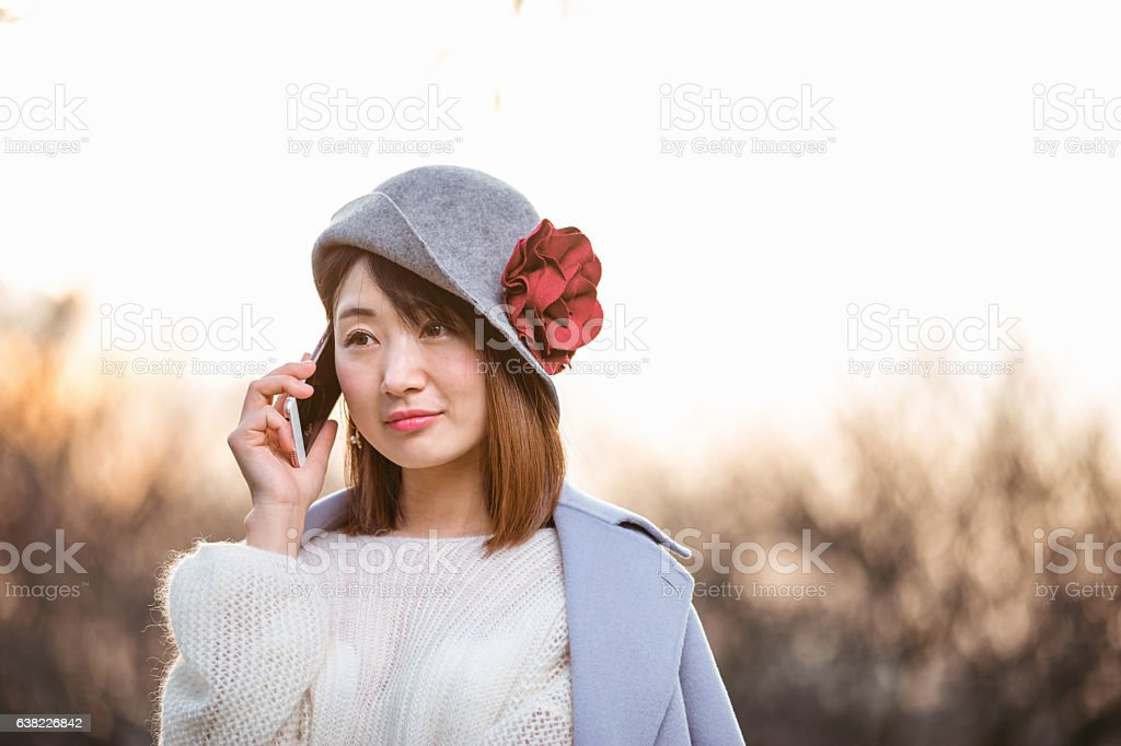 young woman in blue and hat holds cellphone on meadow stock photo