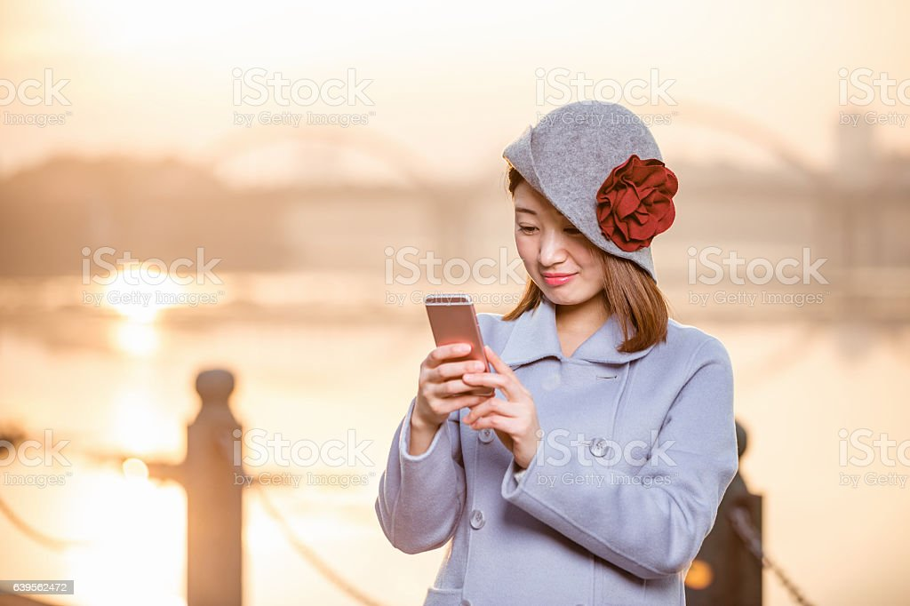 young woman in blue and hat holds cellphone on riverbank stock photo