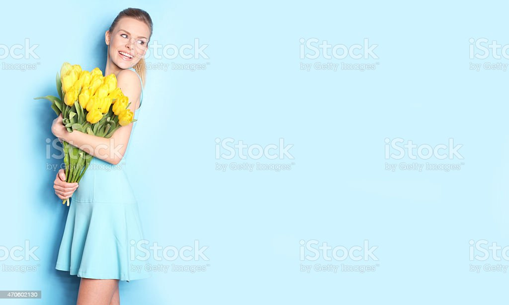 Young woman in blue dress holding an armful of yellow tulip stock photo