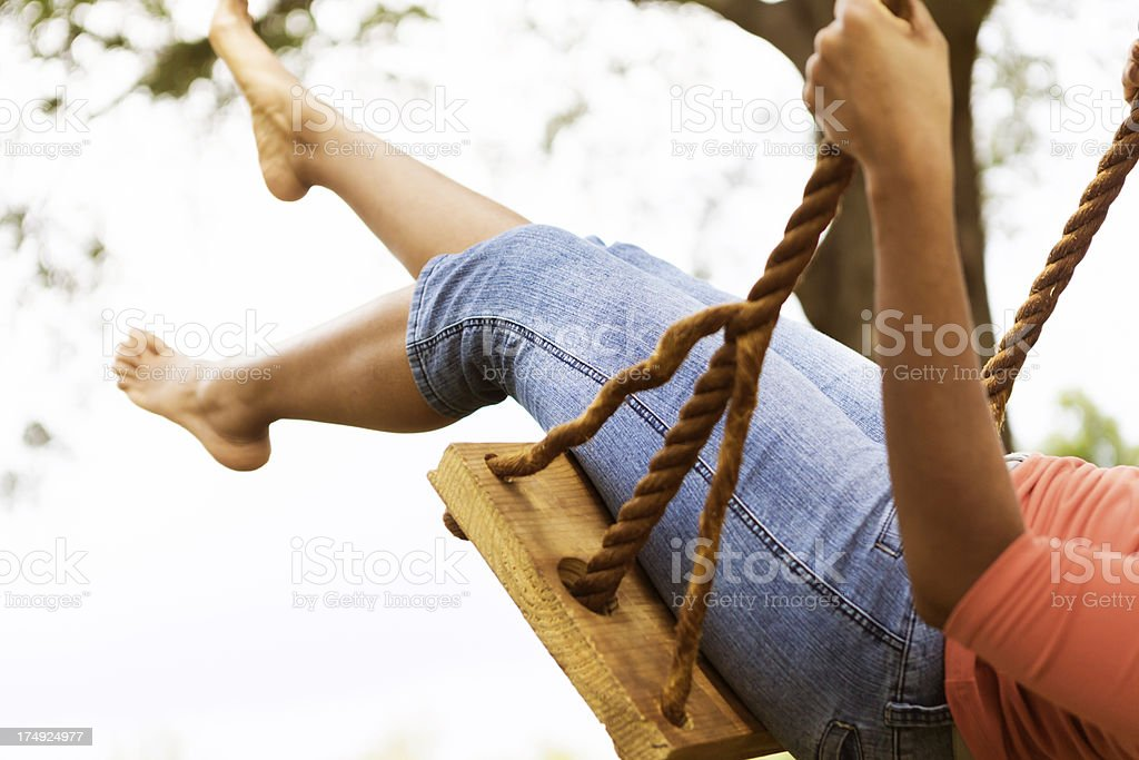 Young woman in blue jeans on swing royalty-free stock photo