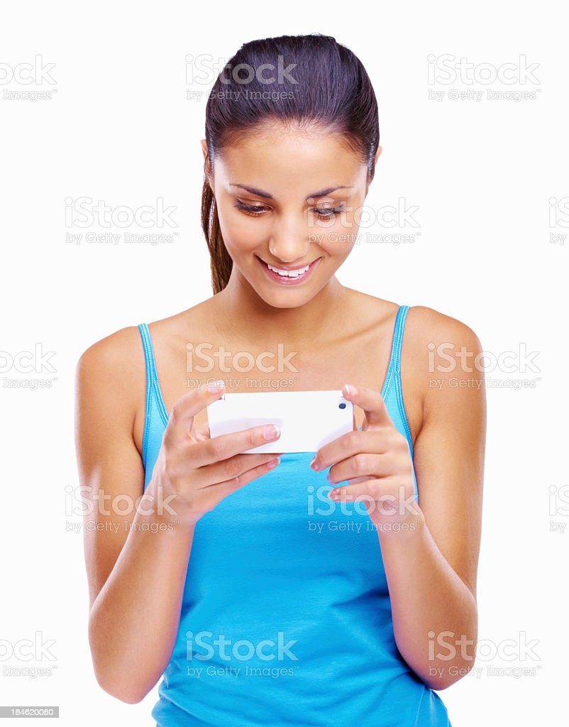 Young woman in blue tank top texting and smiling royalty-free stock photo