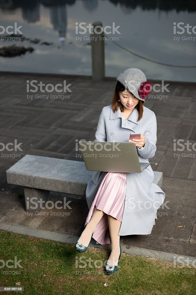 young woman in blue with mobile phone by river stock photo