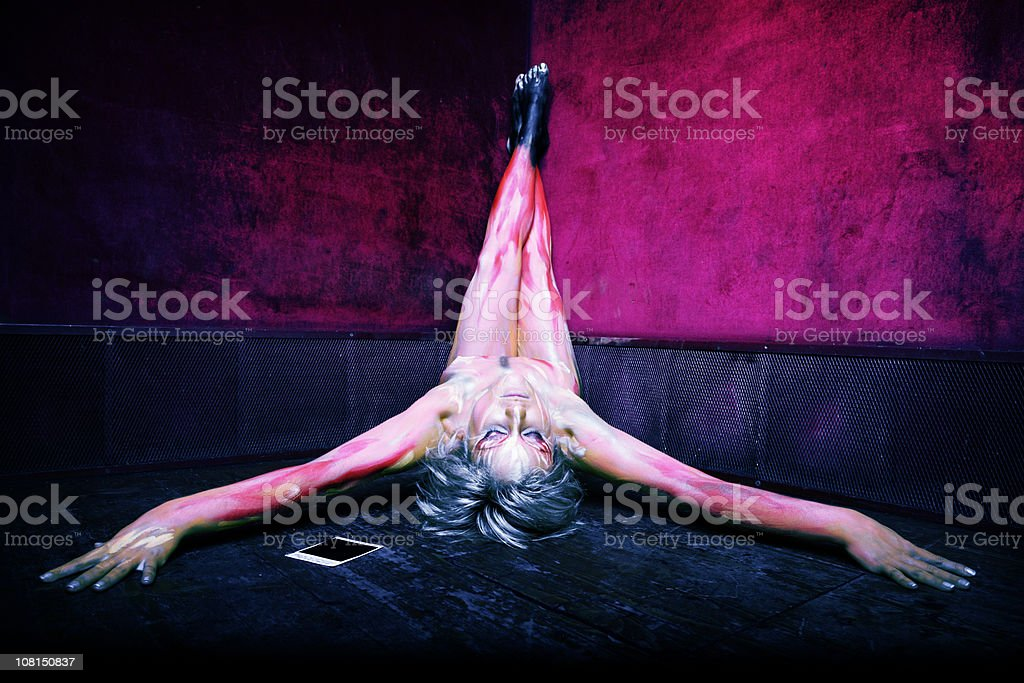 Young Woman in Body Painted Flames Laying on Ground royalty-free stock photo