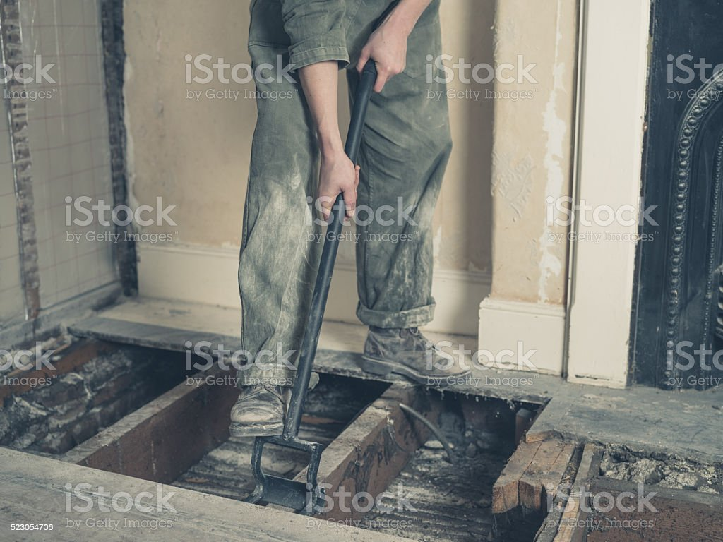 Young woman in boiler suit removing floor boards stock photo
