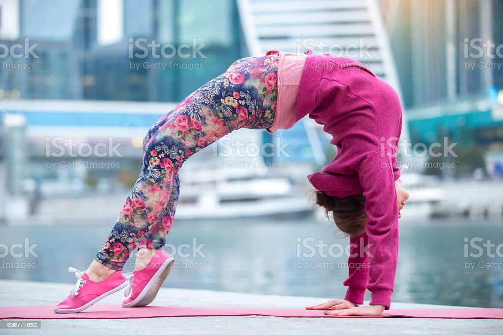 Young woman in Bridge pose against the city and river stock photo