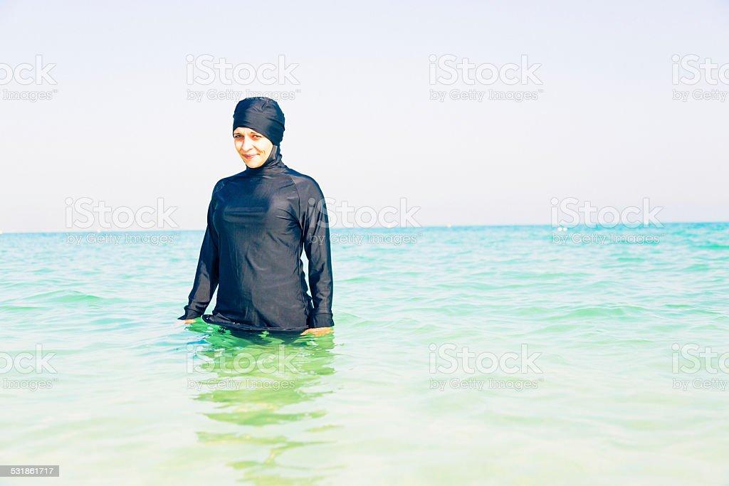 young woman in burkini swimming in the sea stock photo