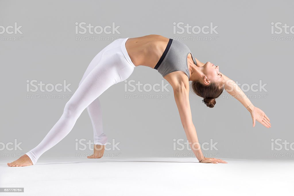 Young woman in Camatkarasana pose, grey studio background stock photo