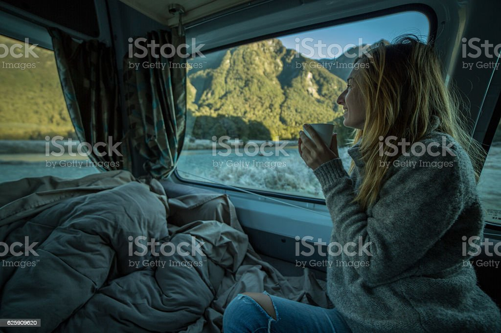 Young woman in camper looks through window, New Zealand stock photo