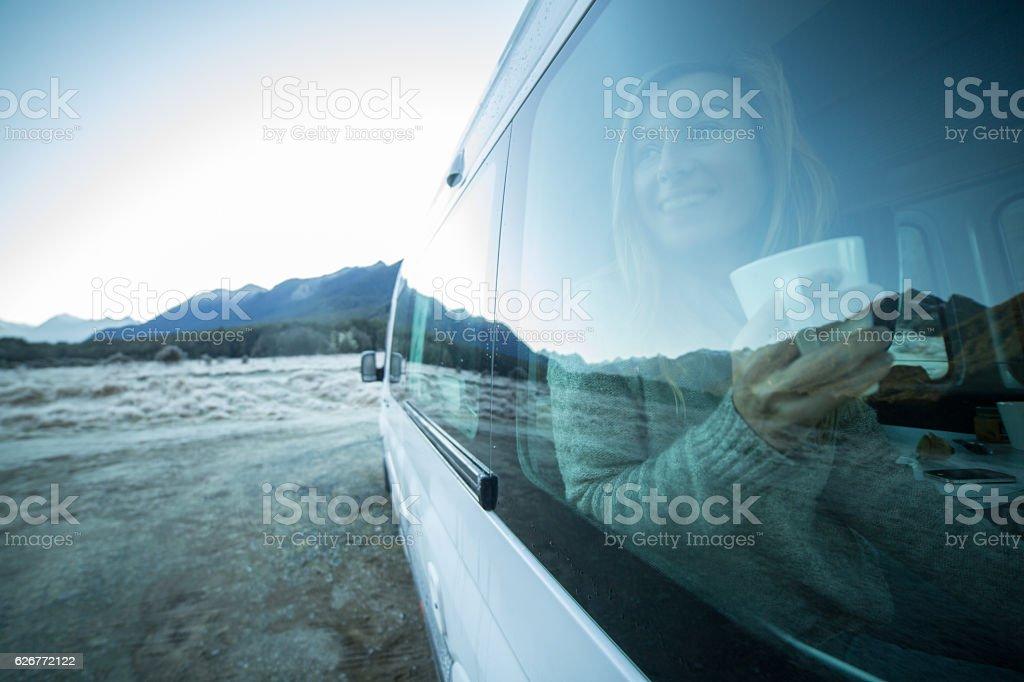 Young woman in camper van drinks cup of tea stock photo