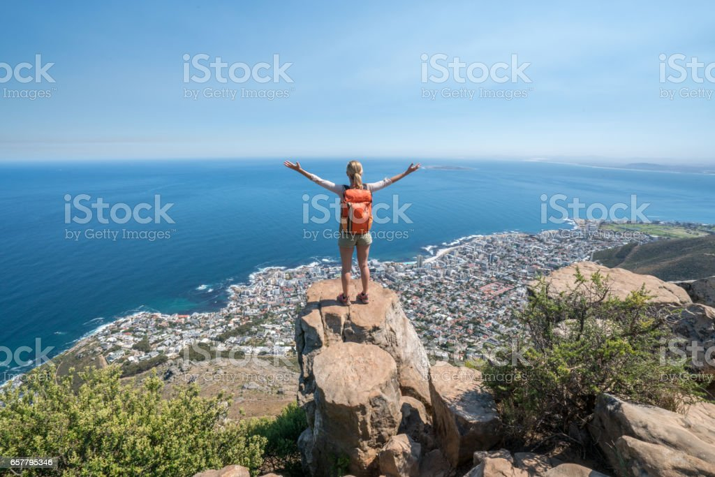 Young woman in Cape Town on top of mountain arms outstretched stock photo
