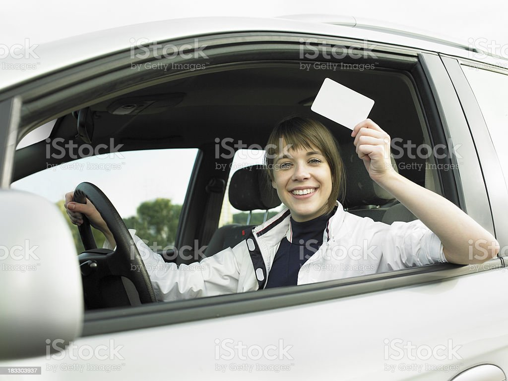 Young woman in car and holding a blank card stock photo