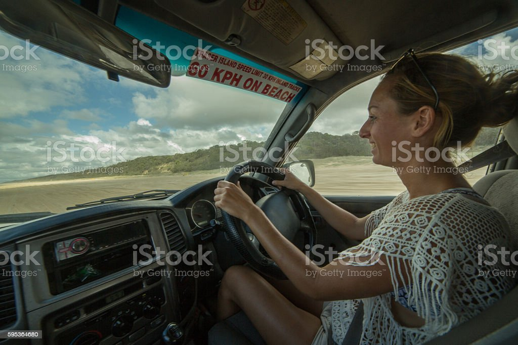 Young woman in car drives on sandy beach, Fraser Island stock photo