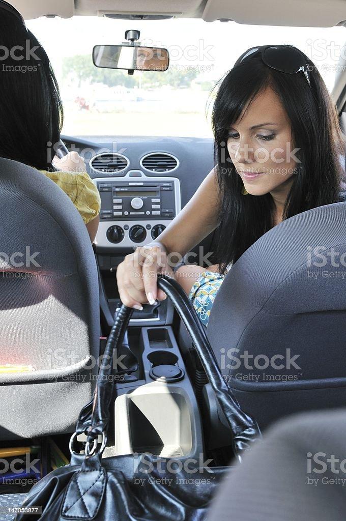 Young woman in car reaching handbag royalty-free stock photo