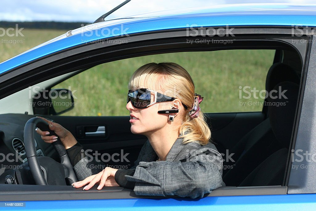 young woman in car with hands free bluetooth royalty-free stock photo
