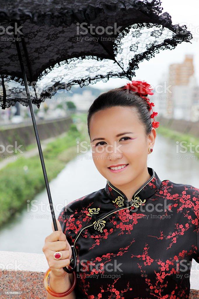 Junge Frau in chinesische Kleid mit Regenschirm gegen city street Lizenzfreies stock-foto