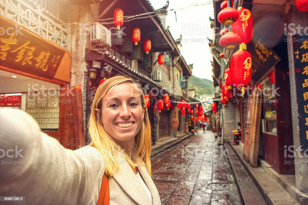 Young woman in Chinese street taking selfie portrait stock photo